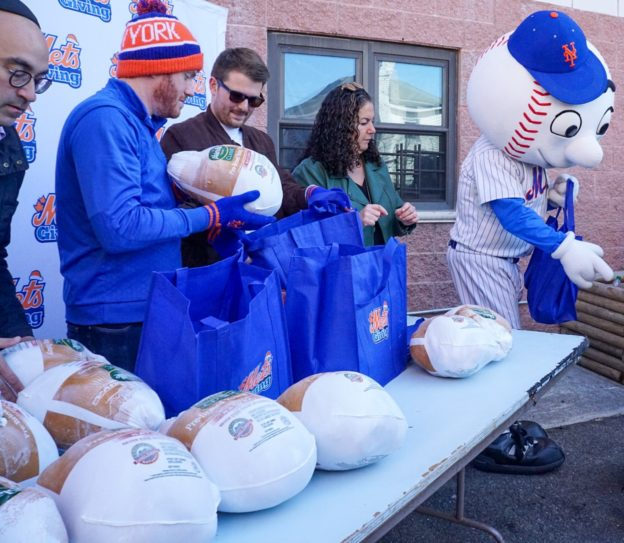 Mr. Met and others from NY Mets hand out turkeys for Thanksgiving as part of Metsgiving